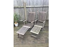 Two wooden patio loungers