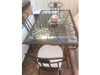 Metal table with a glass top and 4 chairs