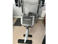 MaxiMuscle home multi-gym bench with barbell and six weight discs, used