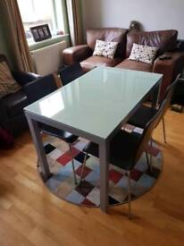 Extending glass top dining table with six chairs