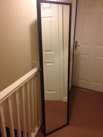 A standing mirror, brown in color, almost new.