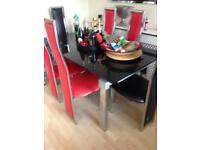 Glass dining table with 4 black and 4 red chairs for sale extending table