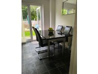 Black gloss extendable dining table and 6 black leather chairs