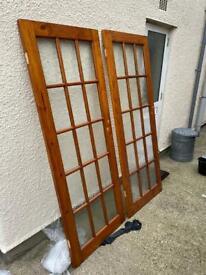 Two varnished heavy pine glazed doors