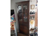 Oak corner display cabinet with leaded glass doors at the top