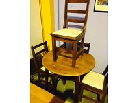 small raund , brown table and four chairs