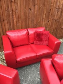 Faux leather red 2 seater sofa and 2 faux leather red arm chairs
