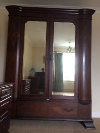 Vintage wardrobe with double doors to hanging space and base drawer. Dark wood.