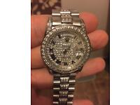 Woman's Rolex iced out watch.