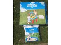 Sand and water activity table with a bag of sand