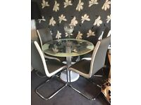 Glass table with four grey and white leather chairs