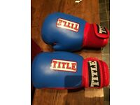 SELECTION OF TITLE SPARRING AND BOXING GLOVES AND HEAD GEAR. LIKE NEW