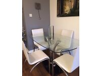 Glass dinning room table and 4 cream chairs in excellent condition