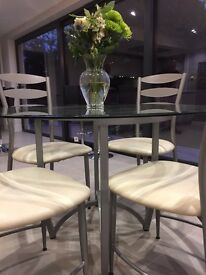 Contemporary round glass dining table with 4 chairs