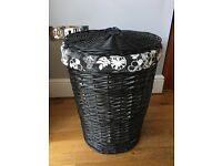Black wicker laundry basket with black and white floral lining