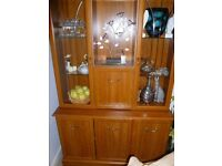 TEAK DISPLAY CABINET WITH 2 GLASS DISPLAY UNITS AND 3 CUPBOARDS BELOW. THIS HAS 3 LOW ENERGY BULBS.