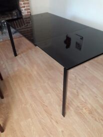 Extending black glass table. Seats 4-8. Used condtion.