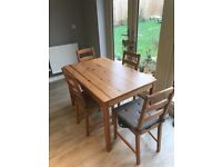 Dining table and four matching chairs with seat pads grey