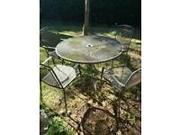 Grey metal table and four chairs. A little rusty. Ideal restoration project.