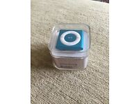 Sky blue IPod shuffle BRAND NEW original box containing instructions, earphones and USB cable.