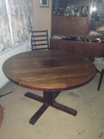 Round, rosewood dining table with centre insert for extending.