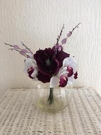 Purple artificial flowers in glass vase