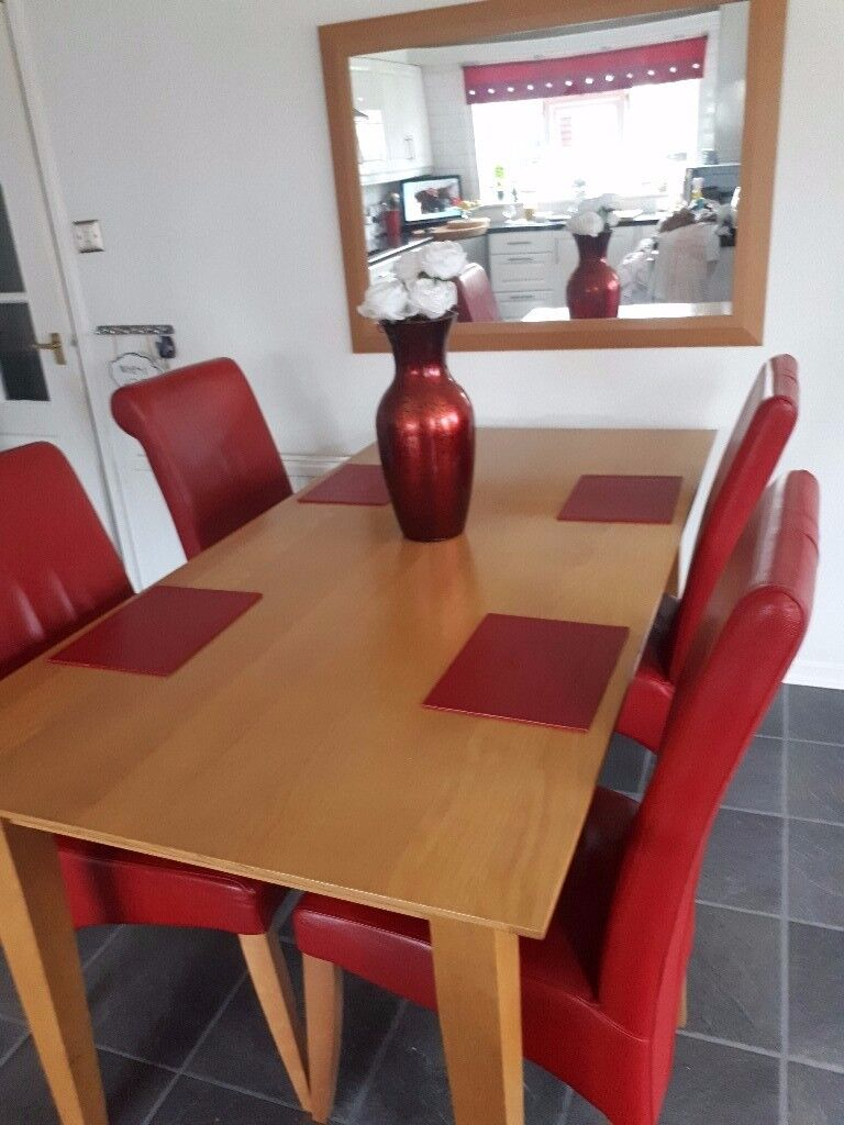 Beautiful long wooden dining table 4 red chairs (2 are carvers) and 2 matching red bucket chairs