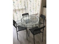 Round glass table with 4 black chairs from ikea