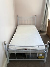 Single white metal bed frame and mattress