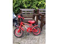 Red Fireman Sam bike with stabilisers