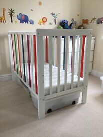 White cot with coloured bars
