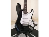 No brand Stratocaster with whammy bar and strap.