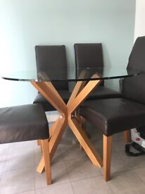 DFS round glass dining table with oak base and 4 brown faux leather chairs