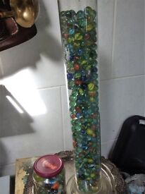 collection of vintage glass marbles in jar and long glass tube