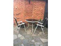 Small glass top table and two foldaway chairs