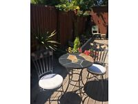 Wrought iron and slate bistro tables and chairs