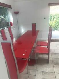 Red glass extendable dining table with 8 chairs
