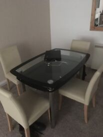 a glass dining table and four chairs