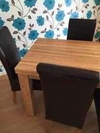 Oak Furniture Land. Oak dining room table and 6 brown leather chairs