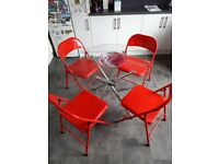 Glass round table and four red folding modern metal chairs, 3 foot diameter, vgc.