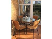 Glass and rattan conservatory table and chairs.