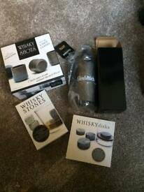 Whisky disks, shot glasses and stones and Glenfiddich water bottle