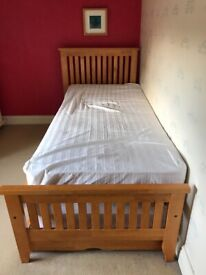Single bed with wooden frame and mattress.