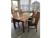 Extending oak dining table and four chairs