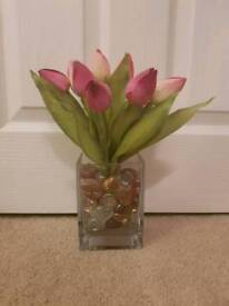 Vase filled with glass hearts and artificial tulips