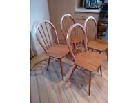 Set of four Ercol Windsor dining chairs in light finish.