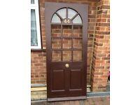 A half glazed external Kentucky hardwood door with brass hinges.