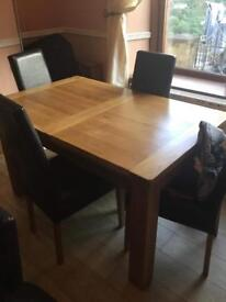 SOLID WOODEN TABLE WITH FOUR LEATHER CHAIRS.