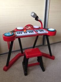 ELC keyboard. It has drums and drumsticks, a stool, microphone and headset. Condition is Like new.