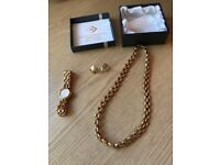 Gold Seiko watch with earrings and necklace
